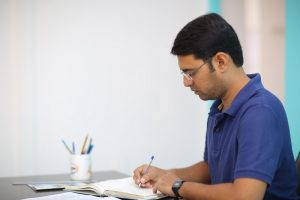 Man in blue taking notes