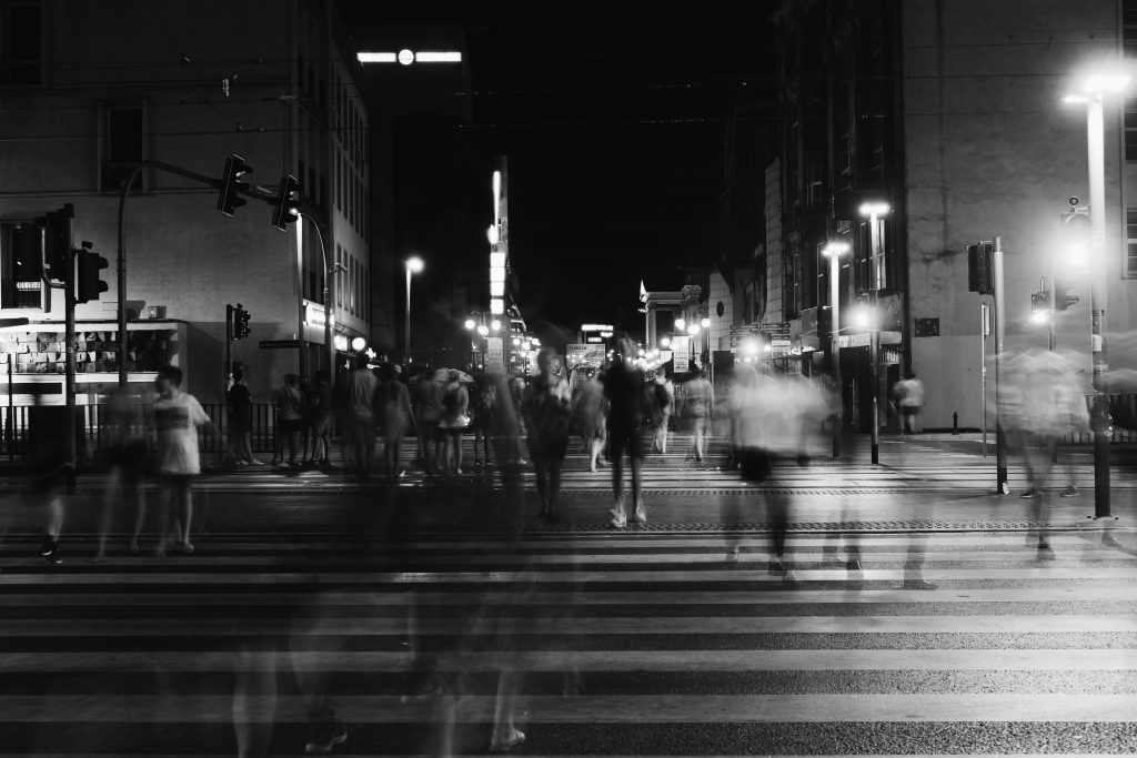 Black and white timelapse photo of people crossing the street