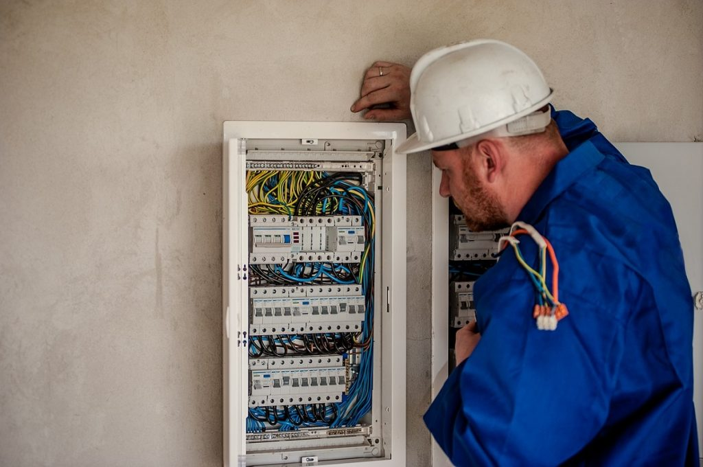 Electrician checking circuit breaker box
