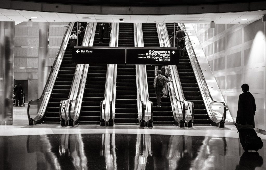 Black and white photo of people using the escalator