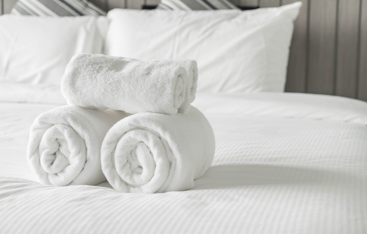 white towels stacked on top of each other on top of a white bed