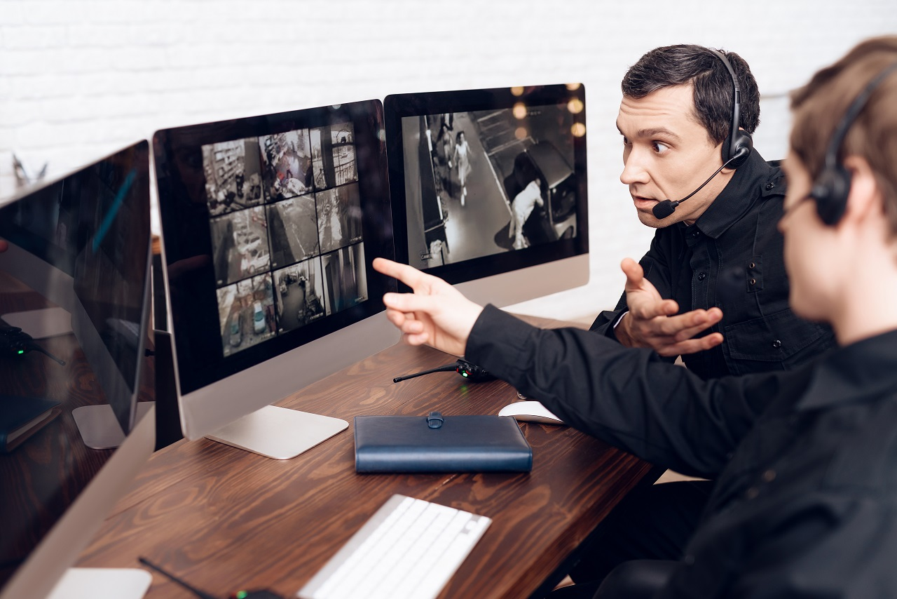Two security personnel reviewing CCTV footage