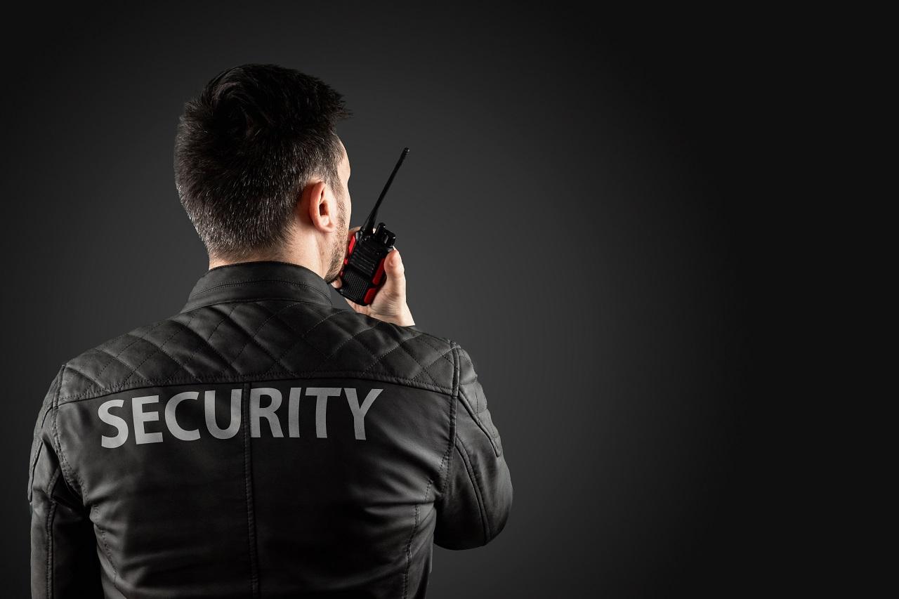 A security personnel in black talking on a walkie talkie