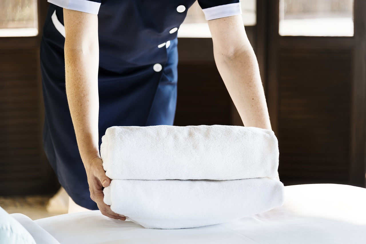 housekeeper cleaning hotel room linen