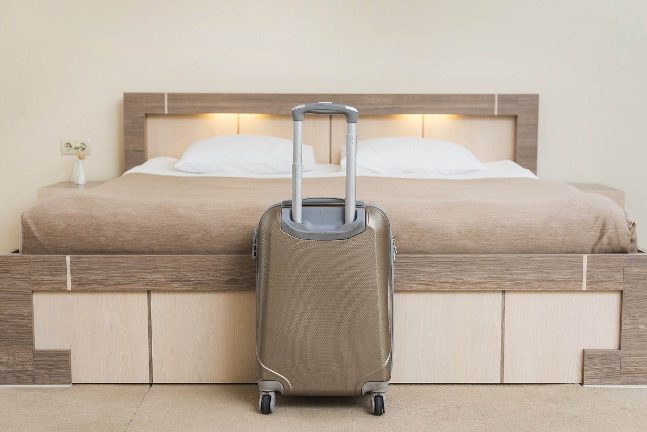A suitcase in front of a hotel bed