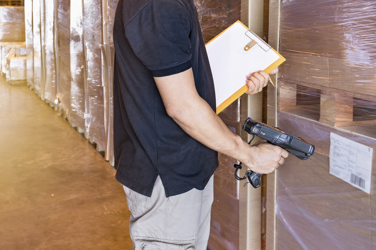A man scanning the RFID of boxes in a warehouse