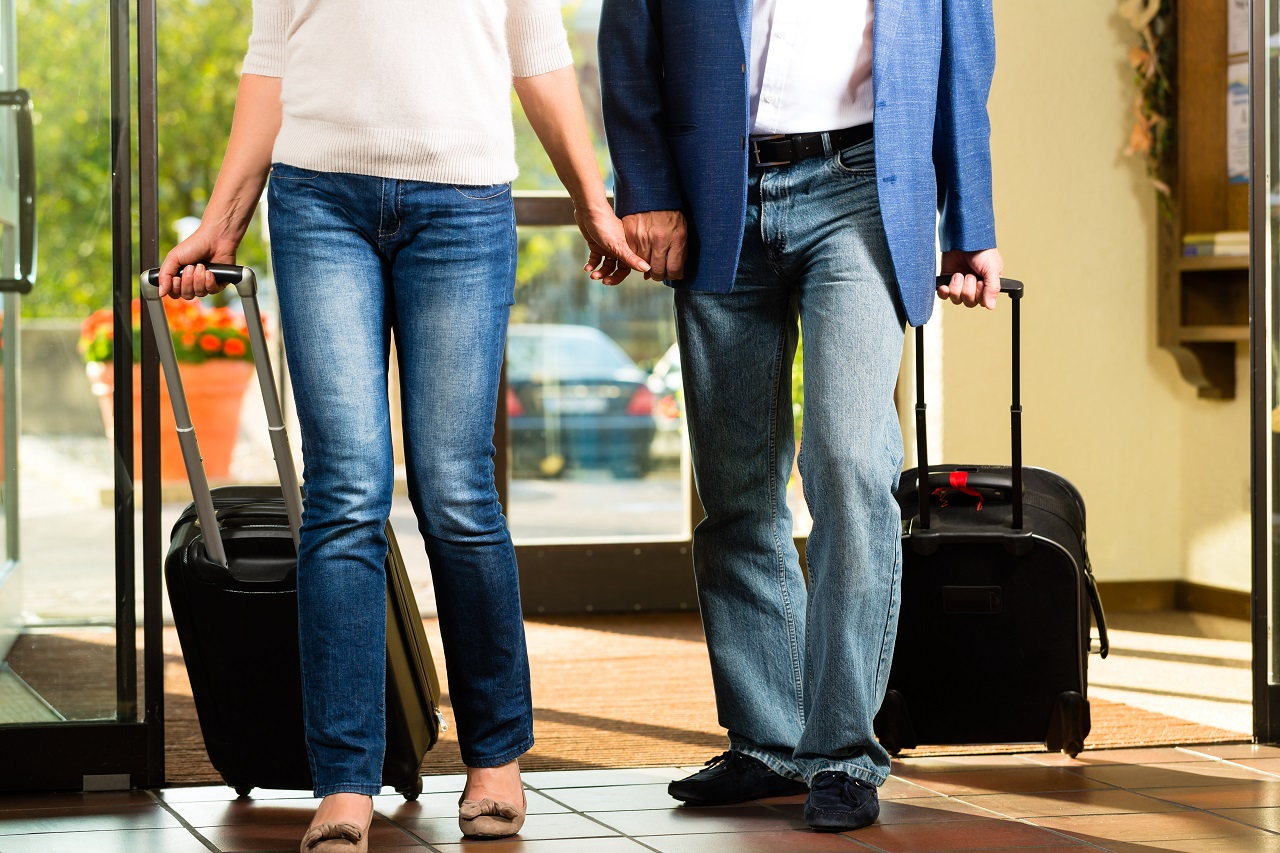 A couple holding hands walking into a hotel with their luggage