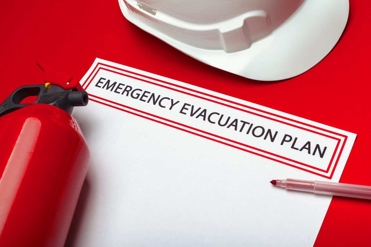 A paper with an emergency evacuation plan surrounded by related items