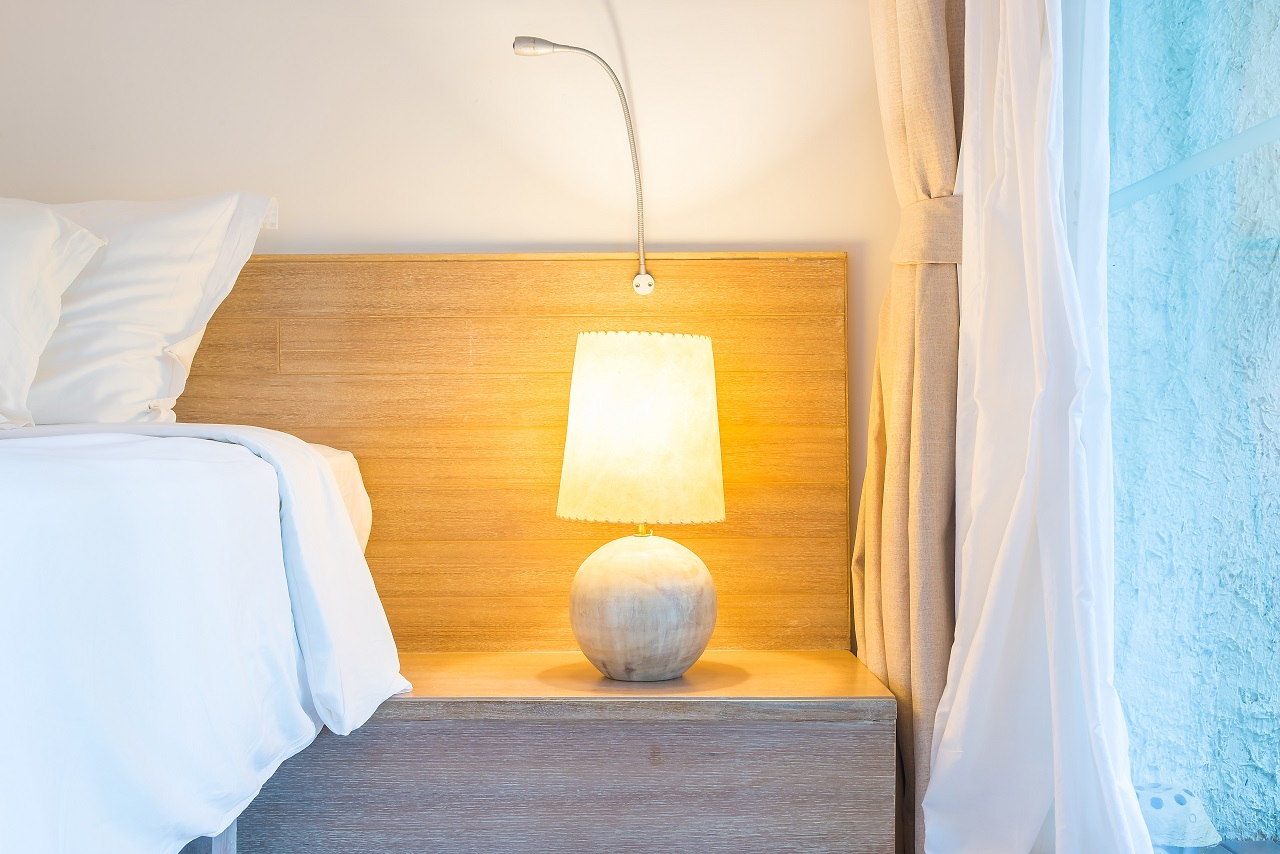 A lamp on top of a hotel bedside table