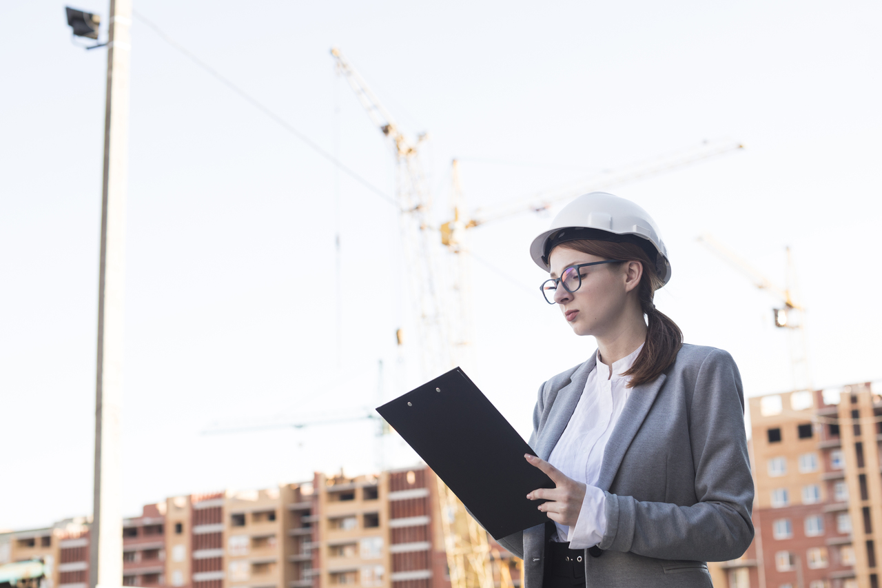 A woman holding a clipboard with a safety hat on