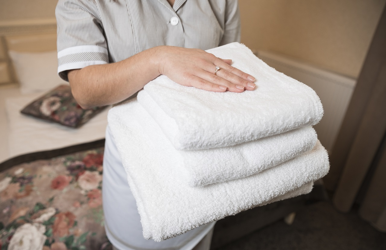 Close up of a woman hotel personnel holding towels