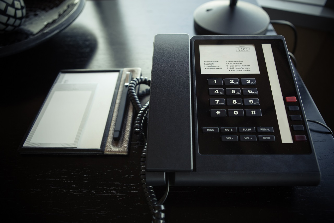 Close up of a hotel landline on top of a bedside table