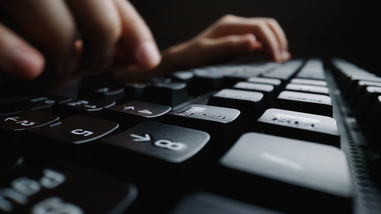 Close up of hands typing on a computer