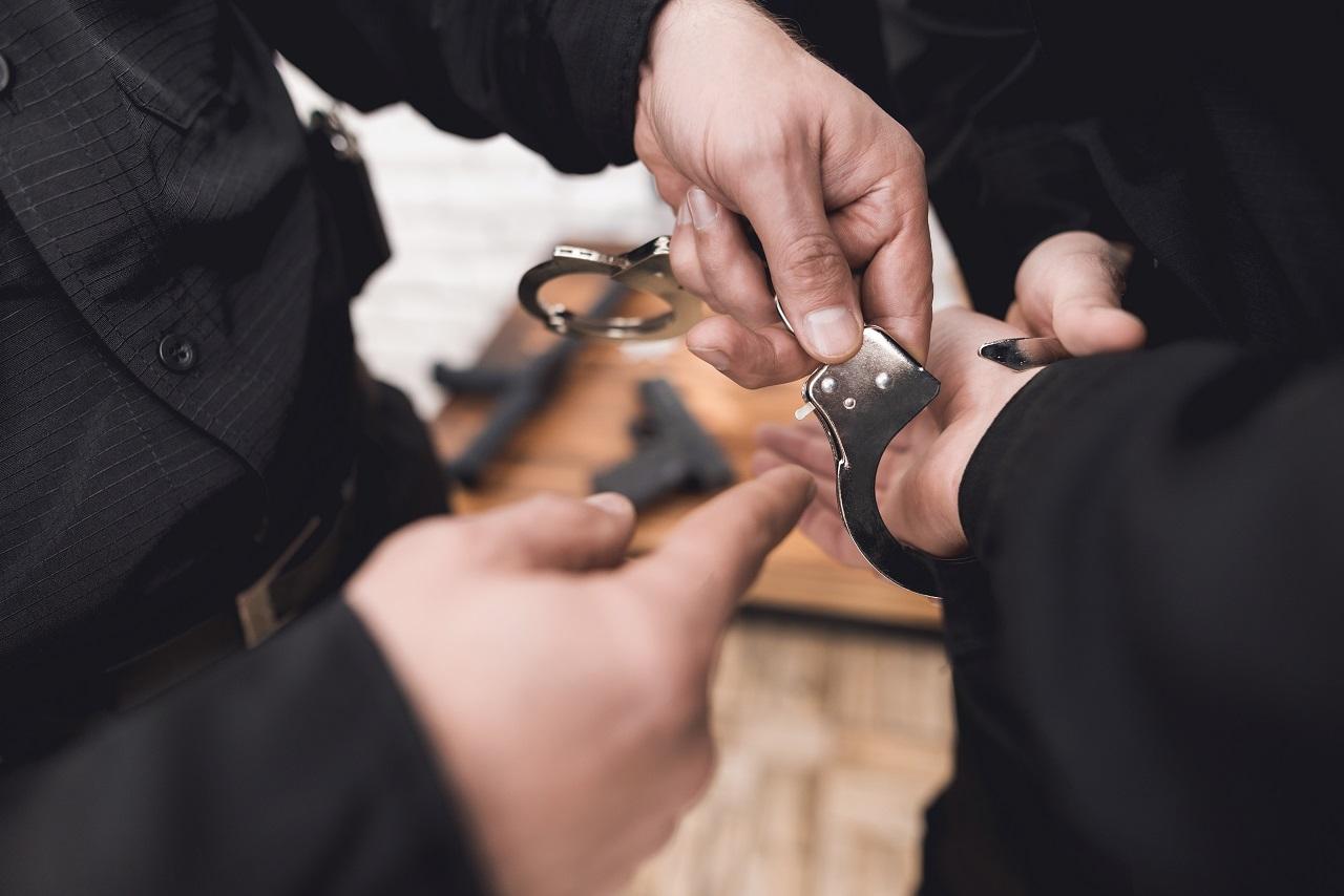 A criminal being put into handcuffs