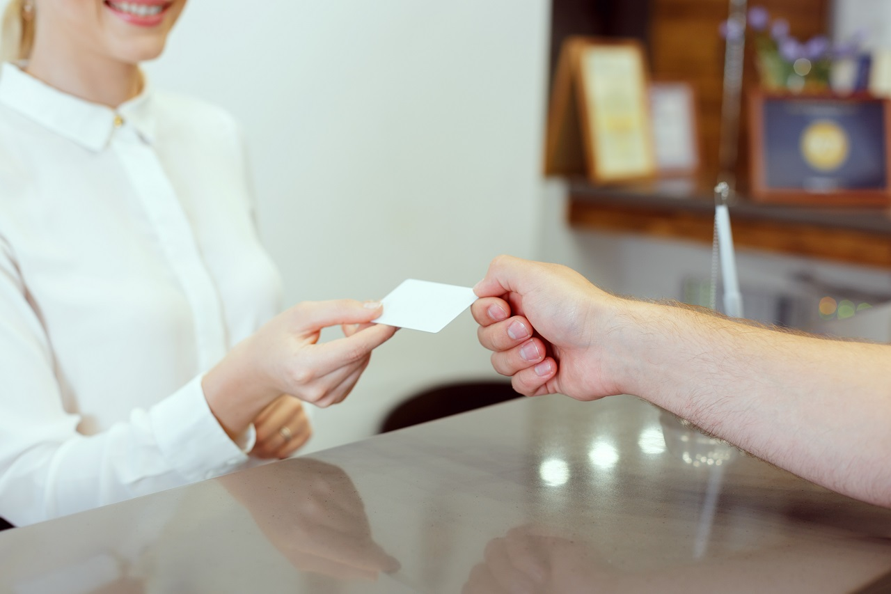 A hotel receptionist giving a hotel key card to a customer
