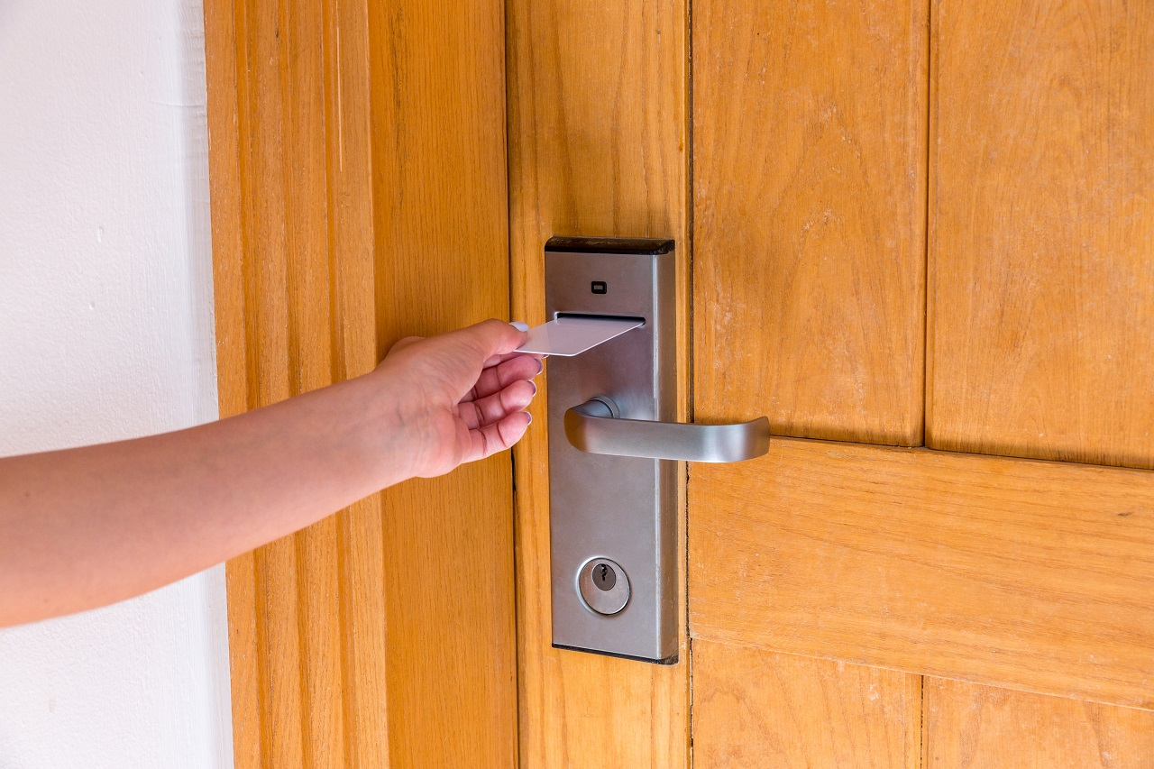 A hand opening a hotel room with a keycard