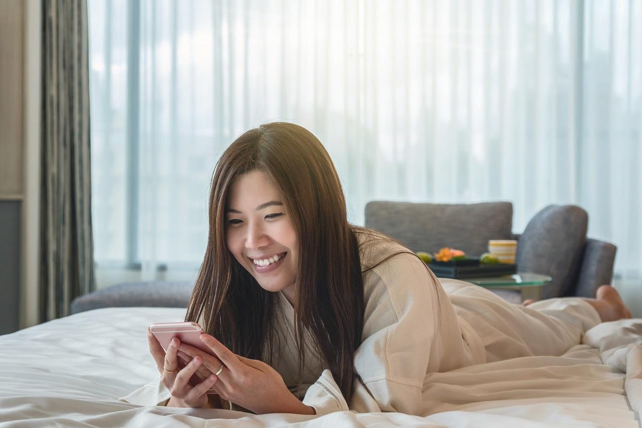 A happy hotel customer in a bathrobe relaxing