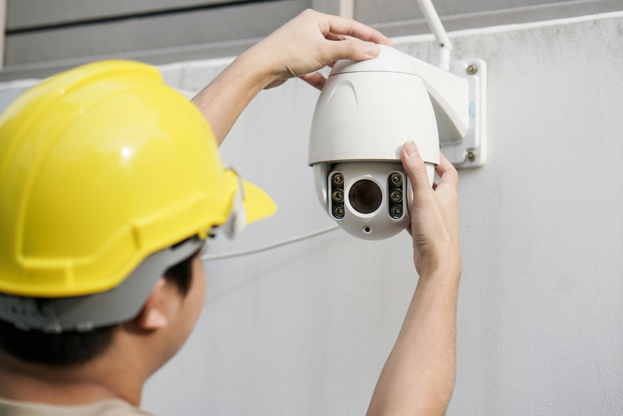An electrician installing a CCTV camera