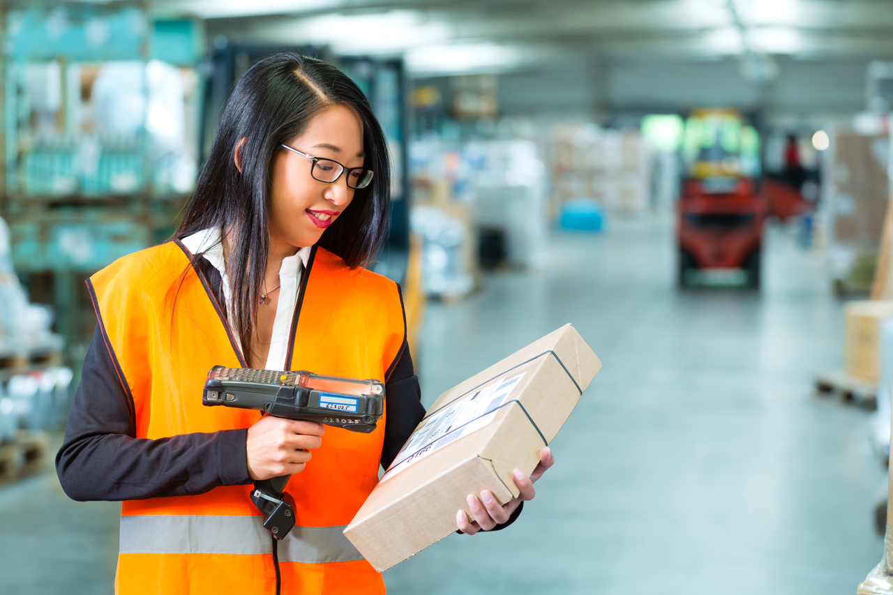 A logistics worker scans a package with RFID