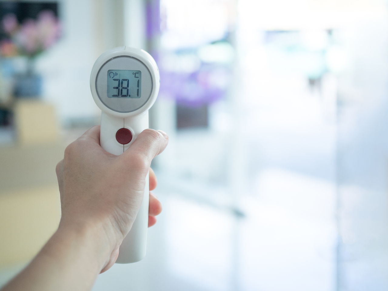 A person holding a contactless temperature scanner