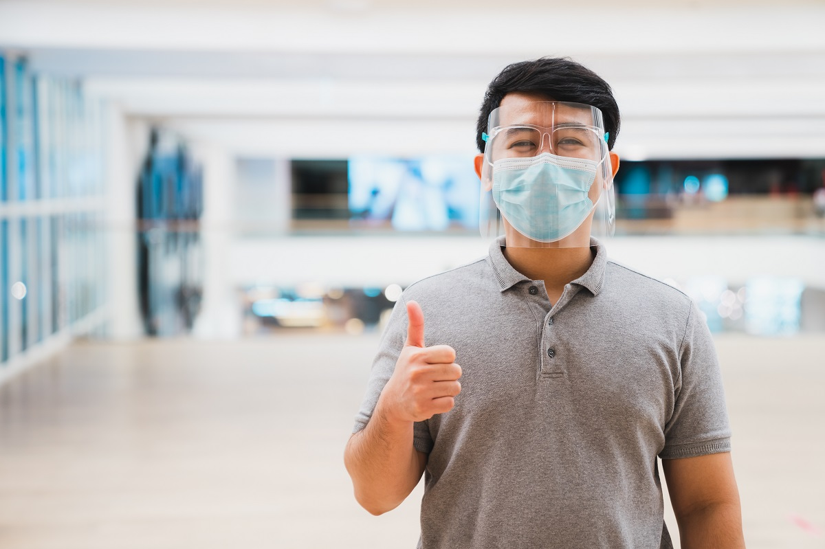 Young asian man wear face shield and mask smiling in shopping ma