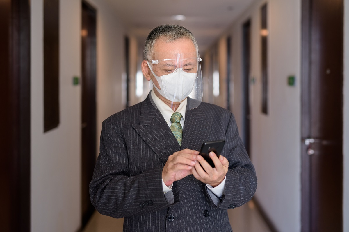 Mature Japanese businessman with mask and face shield using phone in the corridor
