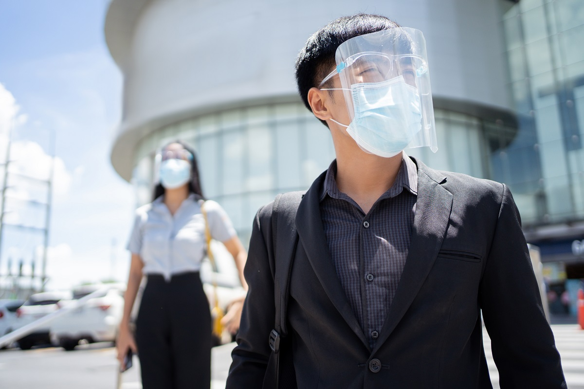 Asian working man, wearing a mass and face shield, protect the virus