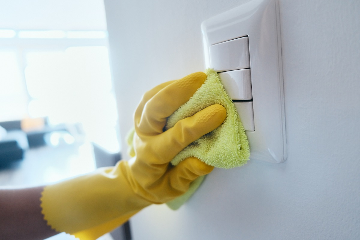 Person With Gloves Disinfecting Light Switches Using Sanitizer