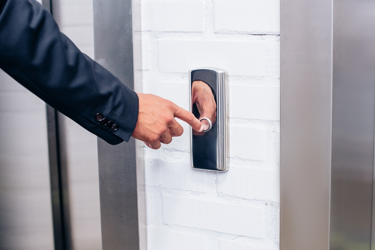 cropped shot of man in suit pressing elevator button