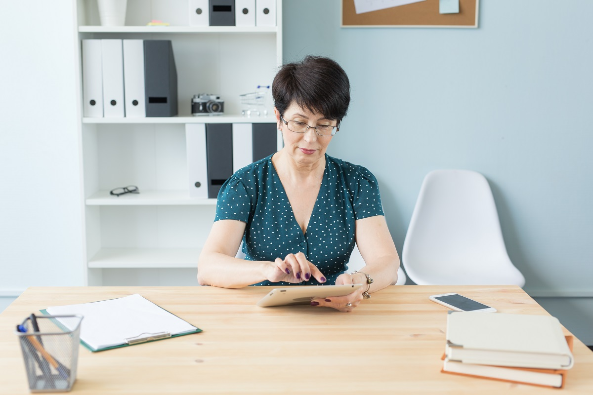 Business, technology and people concept - a serious woman sitting in office and use a tablet