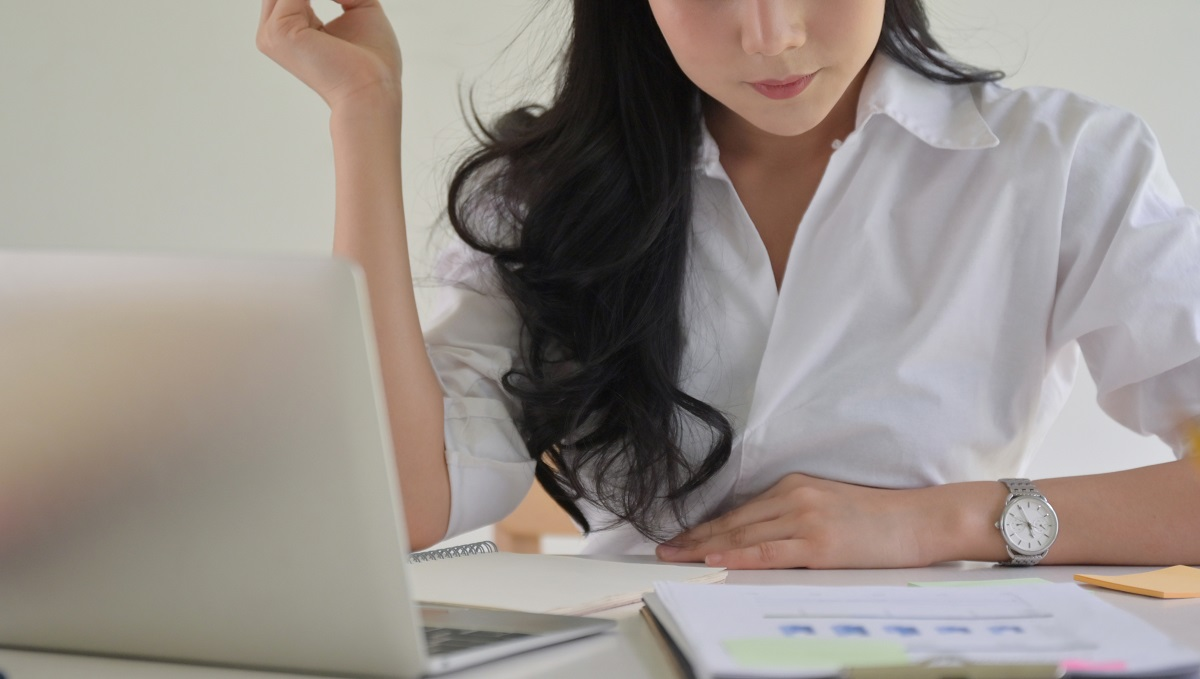 Asian businesswoman with a pen in hand is checking the company p